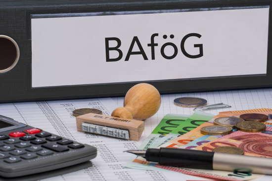 Aktenordner mit Aufschrift BAföG, Stempel, Geld, Taschenrechner, Ausdrucke.