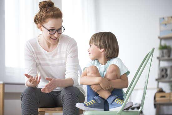 Mutter mit Brille spricht mit ihrem Sohn im Grundschulalter