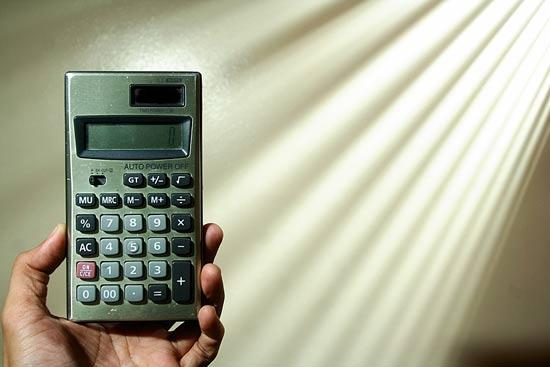 Jemand hält mit der Hand einen Taschenrechner